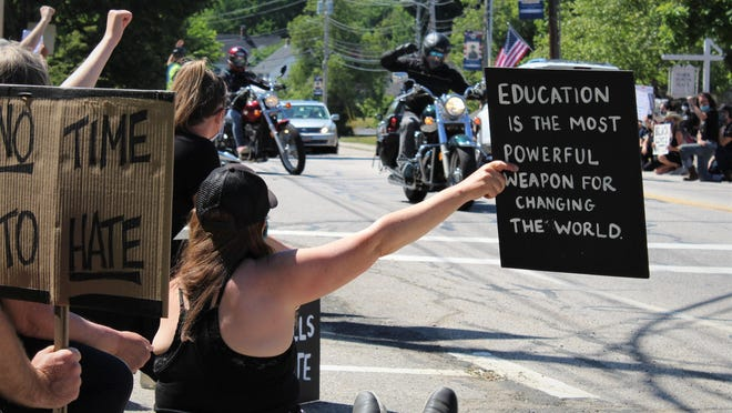 A motorcyclist raises a fist in the air in support of anti-racism protesters who held signs and knelt alongside York Street in York, Maine, on Sunday, June 14, 2020. Organizers circulated a petition calling for a better Black history curriculum in York schools.