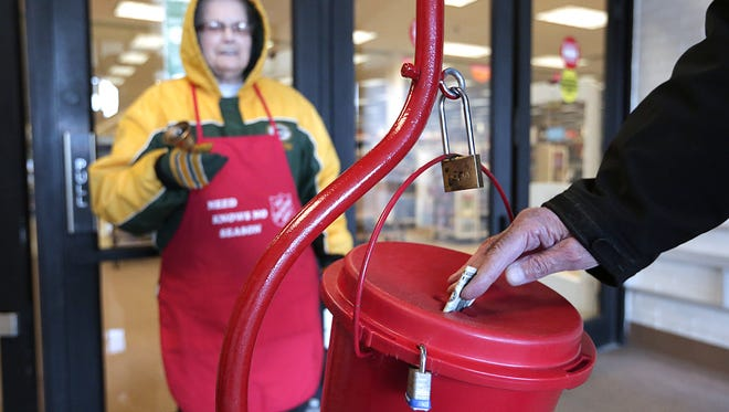 Volunteer Shirley Abler rings a bell for the Salvation Army as a man puts a dollar in the red kettle at Shopko in Fond du Lac.