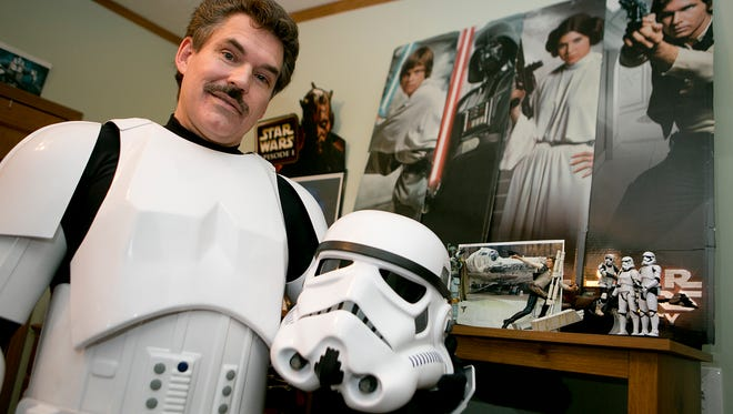 Frank Wileman stands in front of Star Wars memorabilia in his Stormtrooper outfit at his home in Custer, Wednesday, Dec. 9, 2015. Wileman belongs to the Wisconsin Garrison, which is a group of Star Wars fans that make appearances in costume throughout the state.