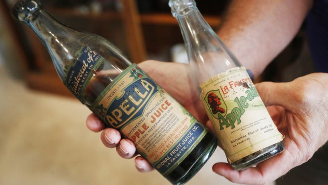 Walt Griffin displays Thieme & Wagner's Apella and Apple-ade bottles. Thieme & Wagner transitioned to the National Fruit Juice Co. during Prohibition.