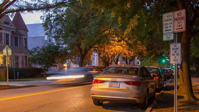Cars fill most of the parking spaces on Cayuga Street between Seneca and Buffalo Streets Monday about 6:15 p.m. in Ithaca. The City of Ithaca is considering expanding the hours for paid parking on the city streets and in parking garages.