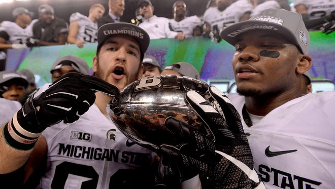 MSU tight ends Josiah Price, left, and Jamal Lyles hold the Big Ten Championship trophy last December in Indianapolis. Price and Lyles were part of two Big Ten championships at MSU, with Price playing a large role in both.