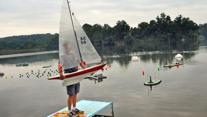Bob Amend of Red Lion carries a 5-foot East Coast 12 sailboat owned by Marty Hayes of Annapolis MD to the water during the Task Force 50's annual Regatta of Radio Control Boats at Lake Redman, Sunday August 17, 2014. John A. Pavoncello - jpavoncello@yorkdispatch.com