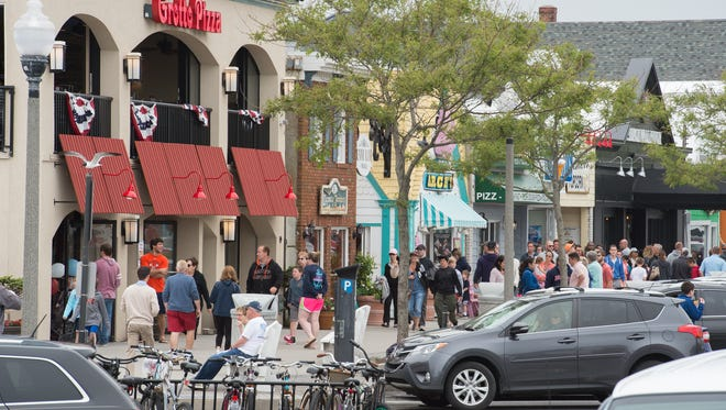 Visitors to Rehoboth Beach walk next to shops along Rehoboth Ave.