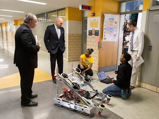 From top left, Henry Ford High School Principal Michael Mokdad, Detroit School District Superintendent Nikolai Vitti and Henry Ford High School english teacher and robotics coach, Gary Mobley, while students Zaakya Artis, 16, bottom left, and Calvin Harvey, 14, work on a robot on Wednesday, May 9, 2018 at Henry Ford High School in Detroit.