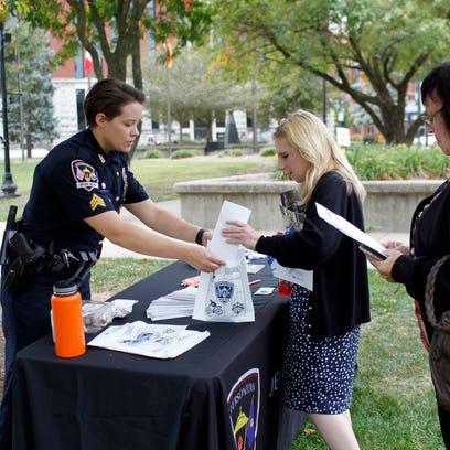Sgt. Brittney Garrett, left, hands out information