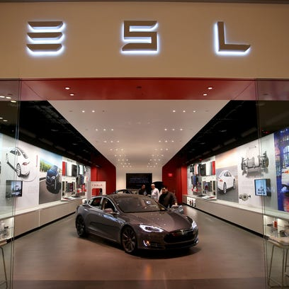 People look at a Tesla Motors vehicle on the showroom