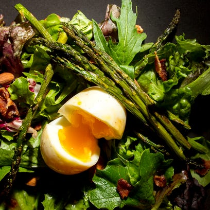 Dr. Knock presents a spring green salad with grilled asparagus, roasted almonds, bacon, a soft boiled egg, and a light vinaigrette.   PHOTO'S CHOICE 2
