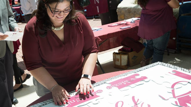 Marissa Fowler, the assistant director of the  Center for Academic advising and Student Support, puts down a piece of a large puzzel that is the logo for the Ignite Aggie Ignite and Discovery campaign, Wedensday April 26, 2017 during the Founders Picnic at Traders Plaza on NMSU's campus.