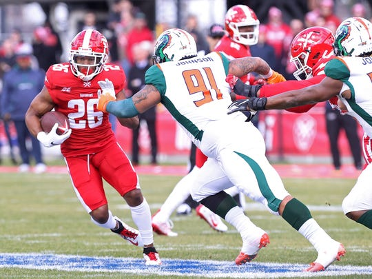 Defenders running back Jhurell Pressley (26) carries the ball past Seattle Dragons defensive end Anthony Johnson (91) in the first quarter during an XFL football game at Audi Field.