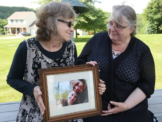 Lyn Coleman and Linda Boyle hold a picture of the children