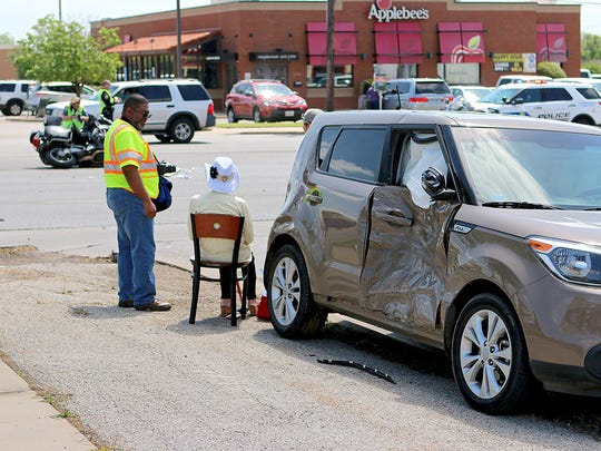Wichita Falls city workers speak with a woman involved in a crash with a police motorcycle l on Kemp Boulevard near Applebee's around 11:30 a.m. Friday.