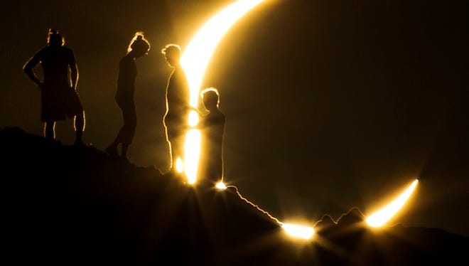 Hikers watch a partial solar eclipse from Papago Park in Phoenix on May 20, 2012.