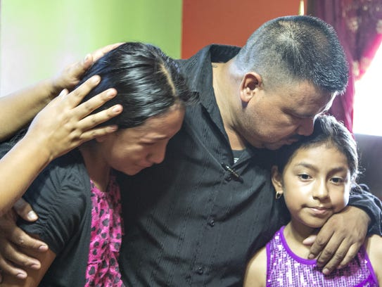 Antonio Velasquez hugs his daughters Anamaria, 12,