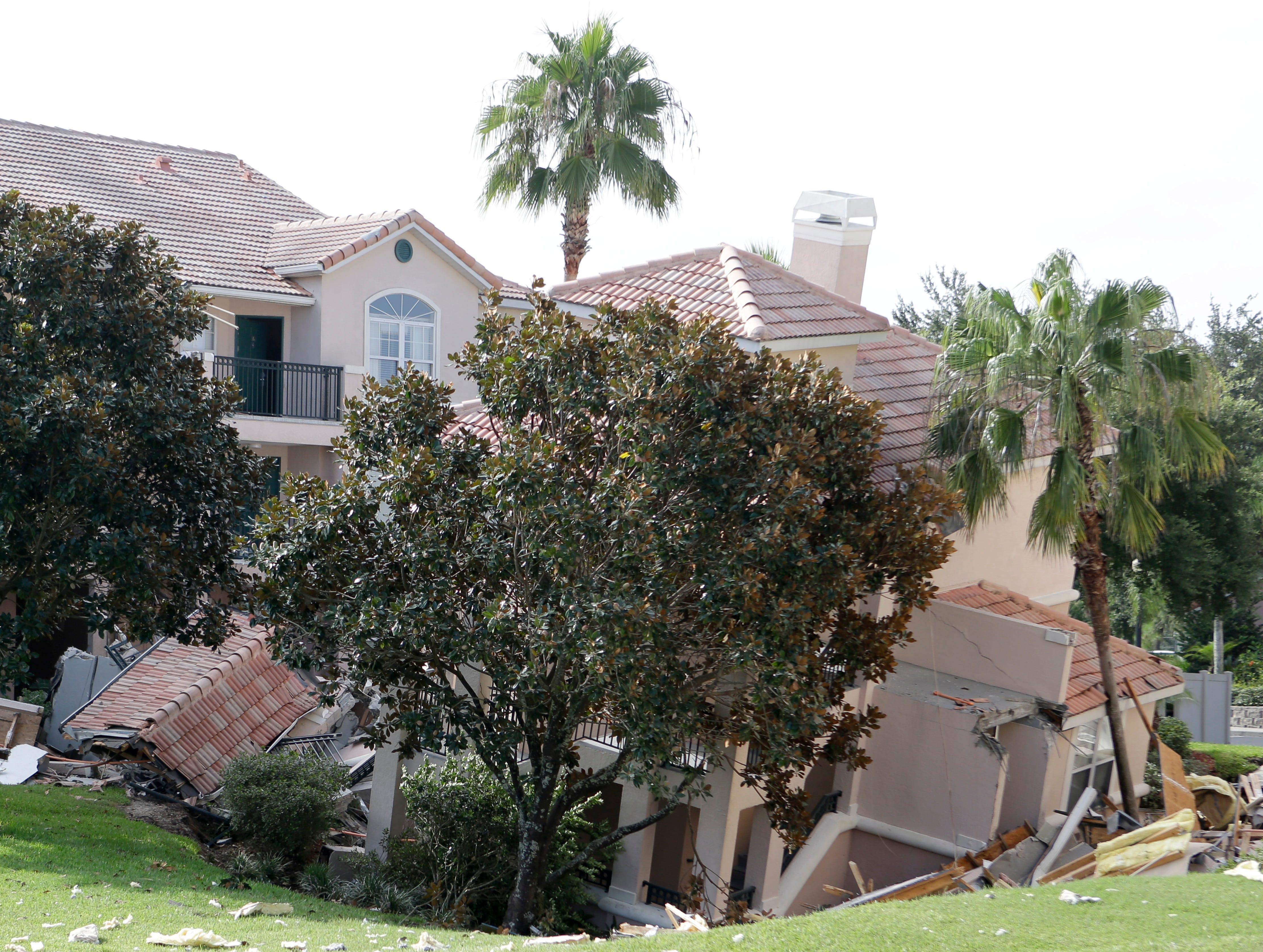 A portion of a building collapses into a sinkhole Aug. 12 in Clermont, Fla. The sinkhole, 40 to 50 feet in diameter, opened up overnight and damaged three buildings at the Summer Bay Resort near Disney World.