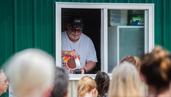 Customers order lunch from the Just Smokin' barbecue food truck at Elstro Plaza in downtown Richmond during the lunch hour on Wednesday, May 9, 2018.