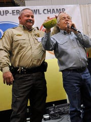 Brown County Sheriff Vance Hill pats Rex Tackett's head as they try to sell Hill's bowl during the celebrity auction at the Empty Bowls Project fundraiser in Brownwood on Thursday. Hill's bowl sold for $400, plus another $400 was donated to the project by members of his department.