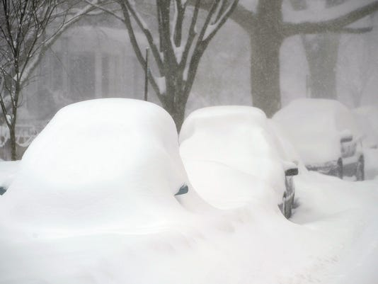 Cars are blanketed under a thick layers