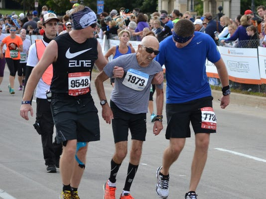 Runner Is Helped Across The Finish Line At Twin Cities Marathon Photo Victoria Grover