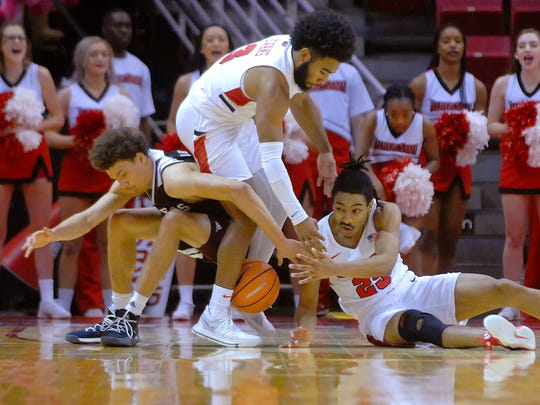 Illinois State guards Keyshawn Evans, center, and Madison Williams, right, force a turnover against Missouri State forward Jarrid Rhodes (15) during the end of the second half Sunday at Redbird Arena in Normal.