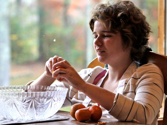 A Feed the Need - Culinary Program participant works on preparing a fruit salad.