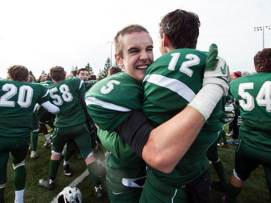 Joey Hester, left, hugs Alex Bond, right, after last year's Division II state championship victory. Hester and Bond are two players on a short list of returnees for the Green Knights, who begin their first season in D-I.