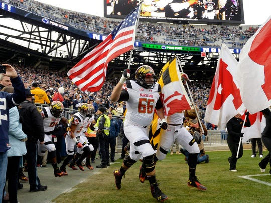 Maryland offensive lineman and Red Lion native Andrew Zeller carries the American flag onto the field before a 2014 game against Penn State.
