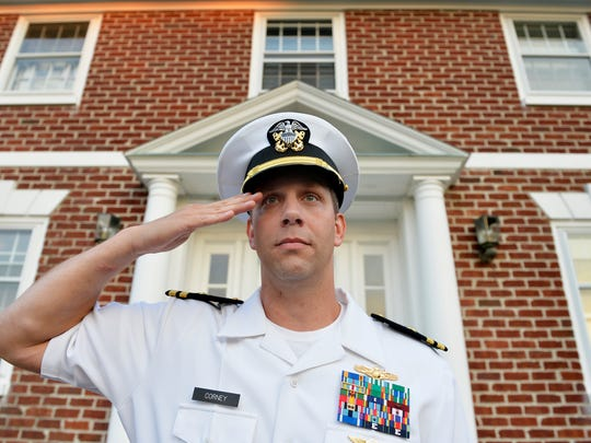 """Joshua Corney stands for a portrait outside his Glen Rock home in 2015. Corney, a lieutenant commander, was serving his 18th year in the U.S. Navy and had recently moved his family to Glen Rock, where he grew up. Until recently, Corney had played a recording of """"Taps"""" outside his home every evening just before 8 p.m. in remembrance of military service members."""