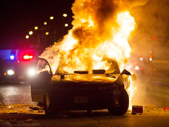 A car burns at the scene of a police riot Aug. 13 in the Sherman Park neighborhood after a fatal police shooting.