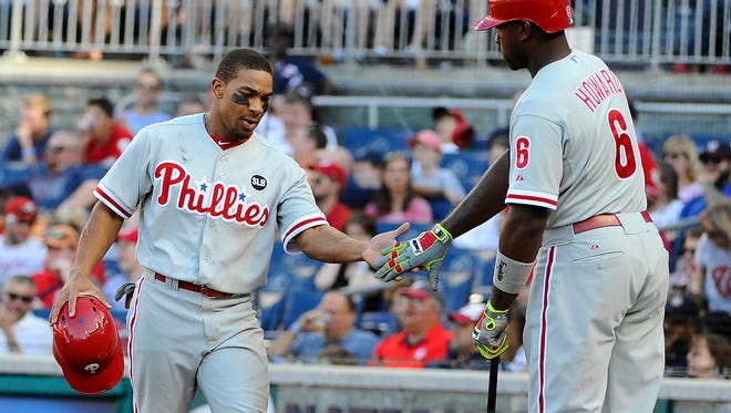 Phillies left fielder Ben Revere (2) is congratulated by Philadelphia Phillies first baseman Ryan Howard (6) after scoring a run against the Washington Nationals during the sixth inning at Nationals Park. The Philadelphia Phillies won 8 - 1.