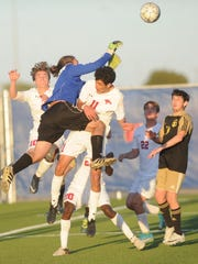 Amarillo High goalie Alan Hadzisabic knocks the ball away on a corner kick as Cooper's Bailey Stewart, left, and John Scaief (11) attack the ball. Cooper won the Region I-5A bi-district playoff game 2-0 on Friday, March 30, 2018 at the Frenship Soccer Complex in Wolfforth.
