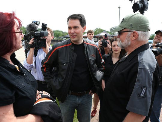 Wisconsin Gov. Scott Walker speaks to Herb and Maria Damstrom of Bondurant, Iowa, during the 2015 Roast and Ride on Saturday, June 6, 2015, which started in Des Moines.