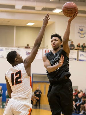 Trinity Shamrocks guard David Johnson (13) shoots the ball during the championship game of the Louisville Invitational Tournament between the Fern Creek Tigers and the Trinity Shamrocks.