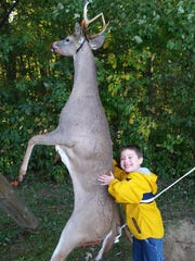 "Dustin Linton's son, Zak, poses with his dad's buck. It took 20 years for Linton to reach his goal of a seven-point ""trophy"" buck."