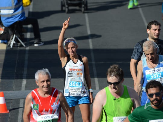 Winter Vinecki, 14, stands at the finish line of the Athens Classic Marathon in Athens, Greece with her hand pointed to the sky, a salute to her father who passed away 5 years ago from an aggressive form of prostate cancer.