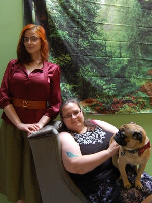 New Crow and Co. bookstore owner Sara Crow, seated, poses with with Ollie, the bookstore Pug, and Store Manager Cat Connolly.