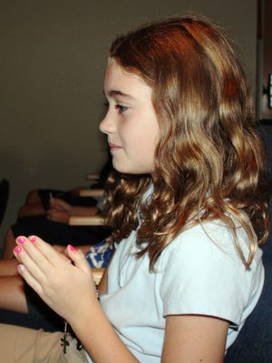 Villa Madonna Academy fourth-grade student Sofia Durstock, of Hebron, prays for peace during the elementary school prayer service.