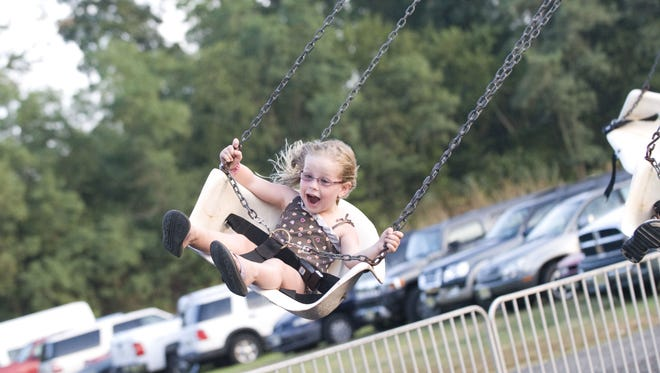 Lucy Michels, 5, of South Harrison, takes a spin on the swings at the Gloucester County 4-H Fair and NJ Peach Festival, July 27, 2012 in Mullica Hill.