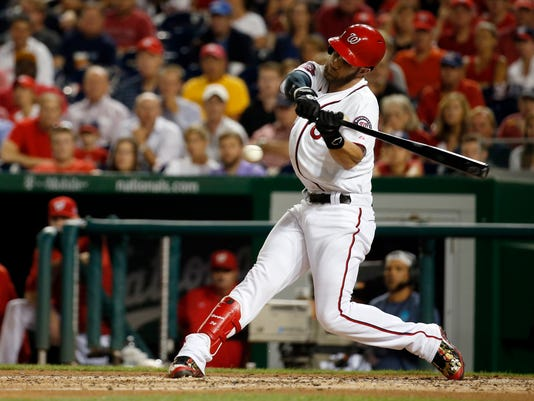 In this photo taken Aug. 27, 2015, Washington Nationals right fielder Bryce Harper (34) bats during a baseball game against the San Diego Padres at Nationals Park in Washington. As they try to forget about 2015 and get started on 2016 at spring training, the best news for the Washington Nationals is that unanimous NL MVP Bryce Harper is still around. (AP Photo/Alex Brandon)