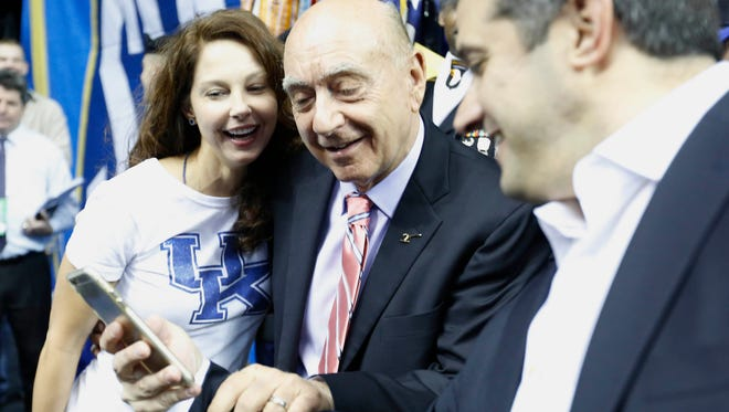Actress Ashley Judd, left, and broadcaster Dick Vitale, center look at a phone before the first half of the NCAA college basketball Southeastern Conference tournament championship game between Kentucky and Arkansas, Sunday, March 15, 2015, in Nashville, Tenn.
