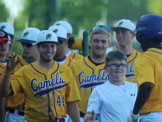 Campbell County players greet Adam Gray after he hit