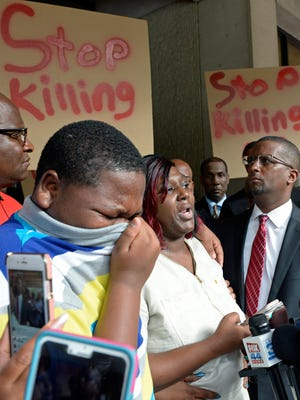 Cameron Sterling, left, Alton Sterling's son, cries, as his mother Quinyetta McMillan speaks about the shooting of Alton Sterling during a press conference and protest at city hall Wednesday, July 6, 2016. Alton Sterling was shot and killed by a Baton Rouge police officer Tuesday outside a store where he was selling CDs.