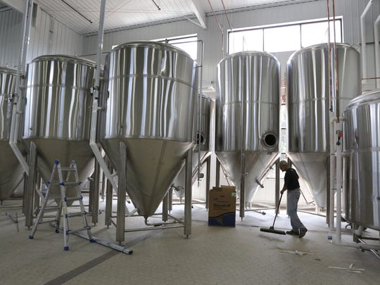In this 2013 file photo, Steve Hummer sweeps the floor near the brewing tanks at Bull Falls Brewery.