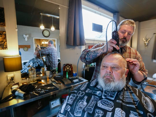 Chad Dunivent gives a haircut to Scott Roussel at the