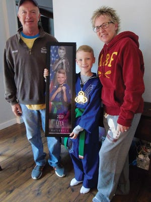 Proud of their son's national Taekwondo first place in his age group are Steve and Shannon McGlynn as Conner wears his medal and holds his award.
