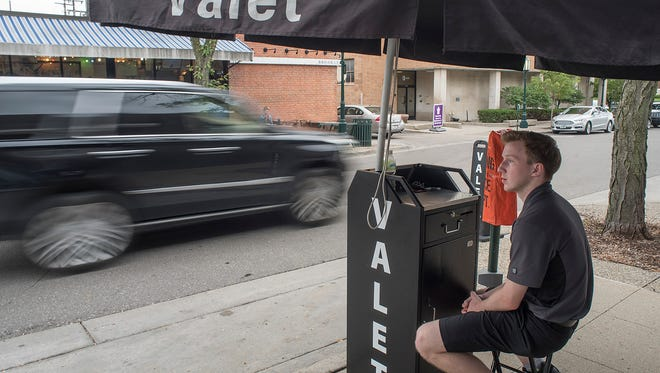 Brandon Holt waits for the next client at one of the valet parking stands in Birmingham.