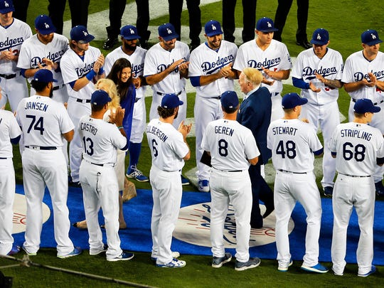 Dodgers players surround Vin Scully and give him a round of applause during a pregame ceremony honoring the legendary broadcaster who is retiring after a 67-year career.