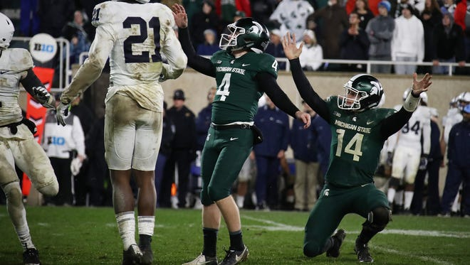 EAST LANSING, MI - NOVEMBER 04: Brian Lewerke #14 of the Michigan State Spartans celebrates a game winning field goal by Matt Coghlin #4 next to Amani Oruwariye #21 of the Penn State Nittany Lions as time expired for a 27-24 win at Spartan Stadium on November 4, 2017 in East Lansing, Michigan.
