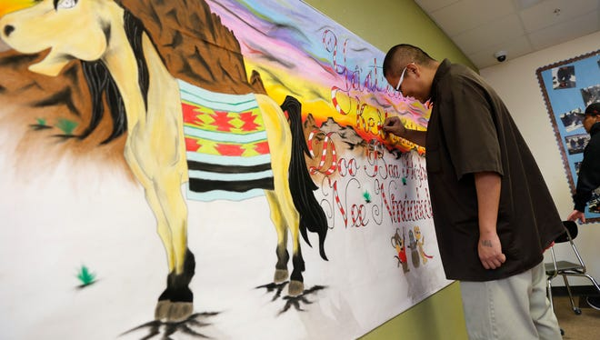 Quinston Watchman, a freshman at Career Prep High School, works on a mural on Monday at the school in Shiprock.