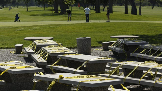 Yellow caution tape covers the tables, to prevent their use at the Haggin Oaks Golf Complex in Sacramento, Calif., Tuesday, April 21, 2020. The Sacramento County health director has designated golf as an essential service to the community, allowing the course to stay open during the coronavirus caused shelter-in-place orders. Golfers are advised to practice social distancing, wash hands frequently, do not congregate in groups and only one person per golf cart.